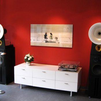 Das Phonomöbel, HiFi-Möbel, ist hier mit Plattenspieler und High-End-Boxen zu sehen. Ein hochwertiger Plattenspieler steht auf dem Kasten.